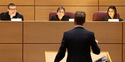 Student speaking to judges in a courtroom setting